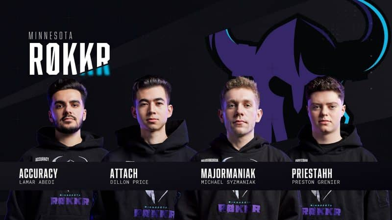 The roster for the Minnesota Rokkr stand facing the camera. Their team logo, a stylized purple and black viking helmet, appears behind them